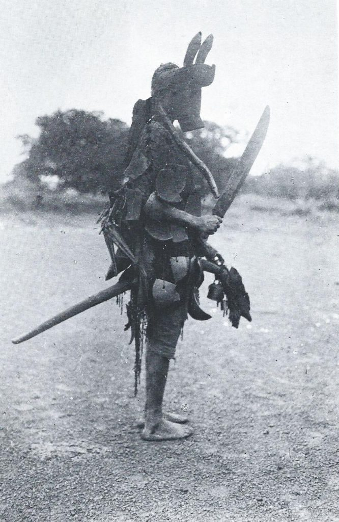 Black and white photography by anthropologist Marcel Griaule of a korèduga, a Mande clown in his ritual equine costume, riding a wooden horse, holding a sword and wearing a horse mask.