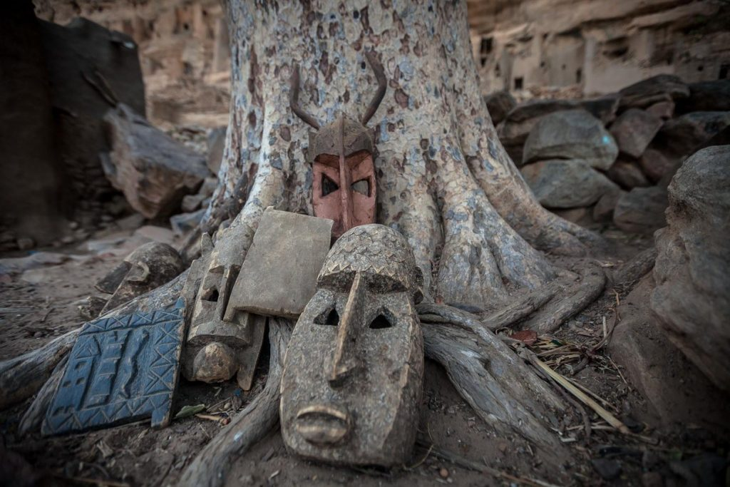 Photograph of several West African masks of the Dogon people, leaning against the foot of a tree in Mali, by Anthony Pappone.