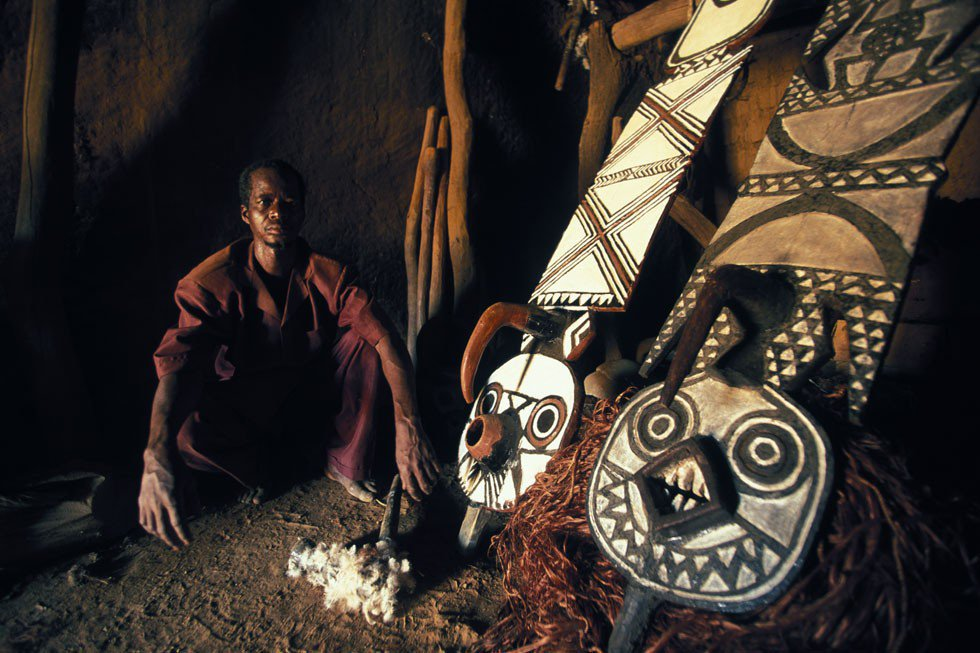 Photograph of a Bwa man sitting near several ornate West African masks during a ceremony in Boni, Burkina Faso, by photographer Bruno Zazottera.
