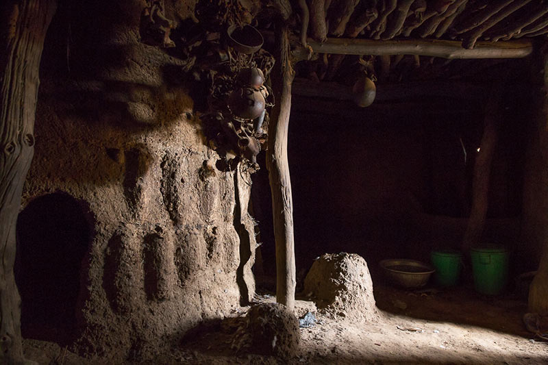 Photography of the interior of a Batammaliba Tata Somba or Takyenta house, showing the ancestral shrines and architectural beams.