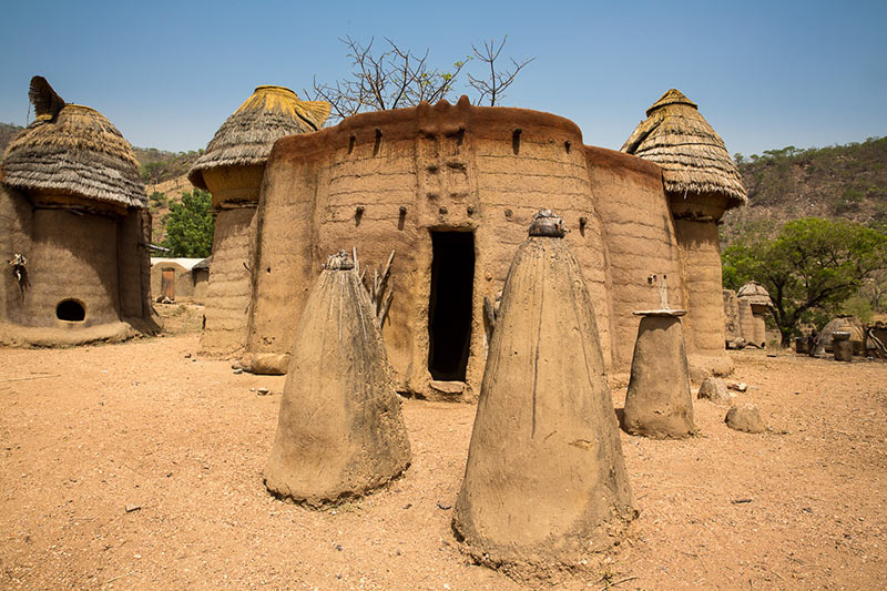 Photography of the front of a Batammaliba Tata Somba or Takyenta house, showing architectural features such as a decorated entrance facade, two granaries, and lisenpo mounds in front of it.