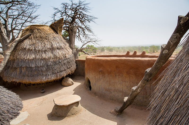 Photography of the terrace of a Batammaliba Tata Somba or Takyenta house, showing the granaries that are accessed via a forked ladder, as well as the tabote house hole covered with a stone.