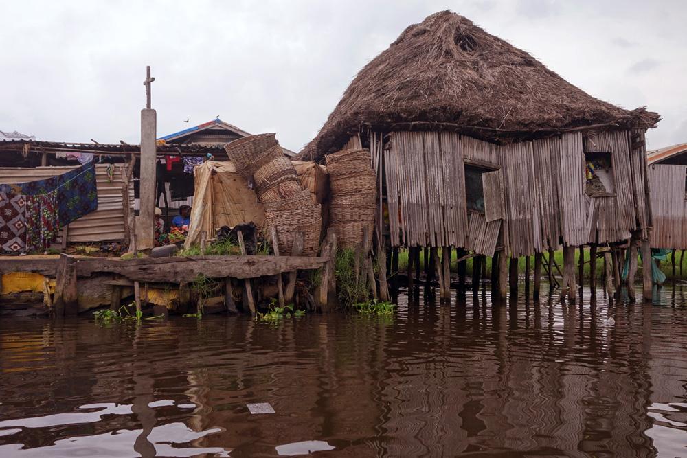 Photographie de l'architecture ouest-africaine au Bénin, une structure faite de bambou, construite au dessus de la rivière.
