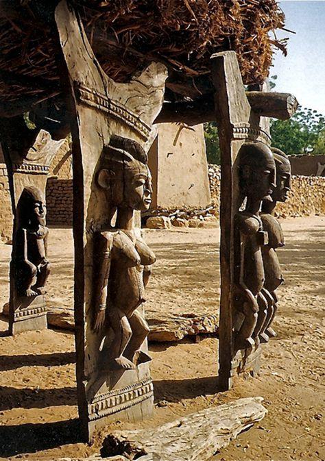 Photographie d'un toguna ou case à palavre dogon, avec des statues engravées dans ses pilliers, un bel exemple d'architecture ouest-africaine.