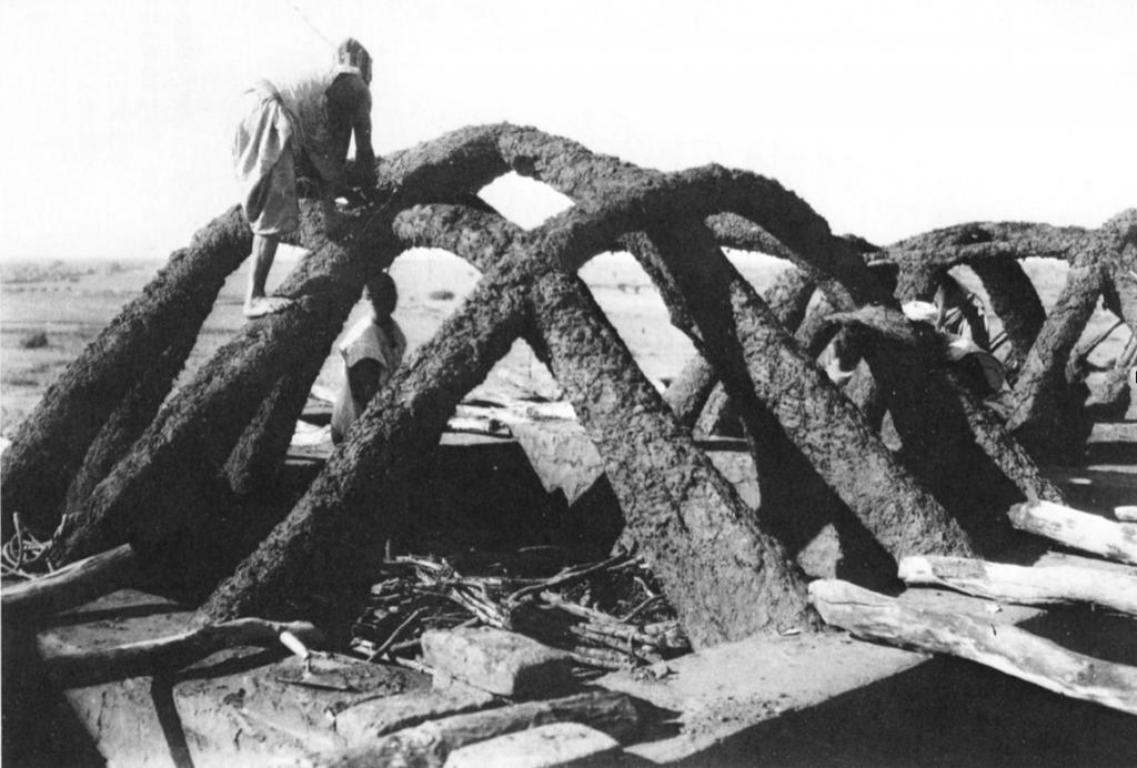 Photographie en noir et blanc d'hommes haoussas en train d'ériger une voûte en terre, une construction typique de l'architecture ouest-africaine de cette région du Niger.