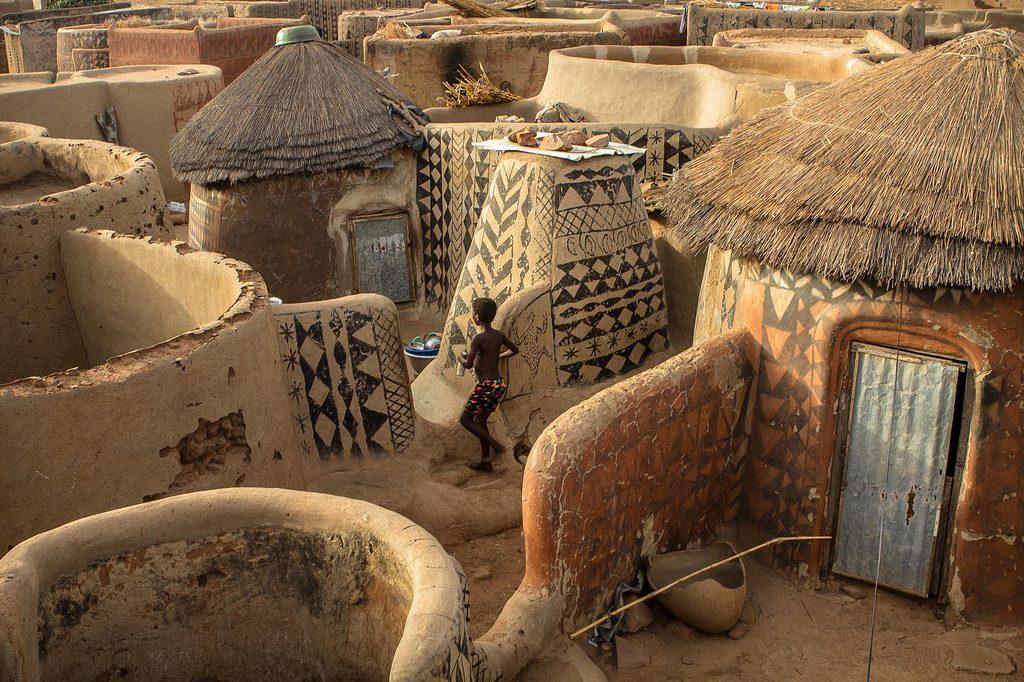 Photographie d'une architecture ouest-africaine au Burkina Faso: un village de bâtiments en terre battue appellés Sukhala, peints avec des motifs géométriques.