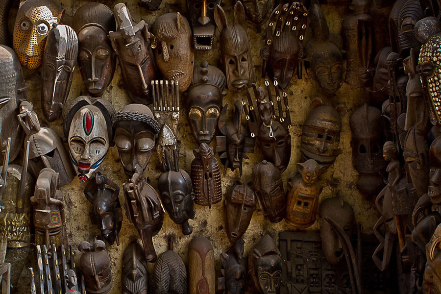 Photograph of the mud-brick wall of a hut in Mali covered in West African masks.