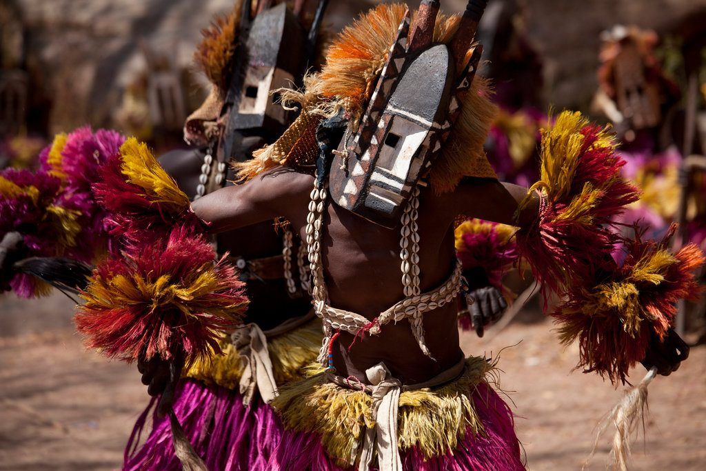 Photograph of masked Dogon dancers in colorful costumes with cowrie shells during the Dama masquerade.